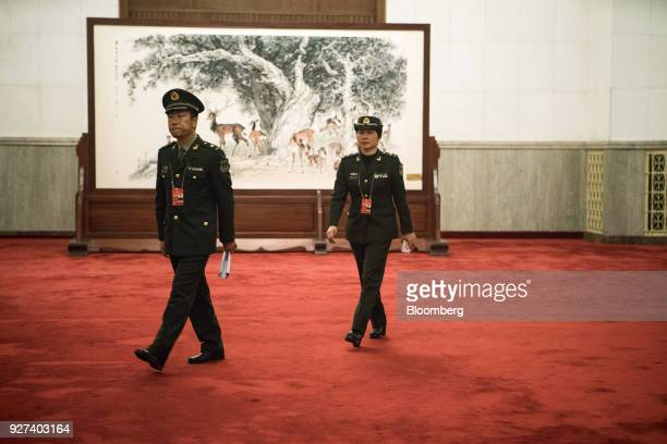 Members of the People's Liberation Army walk through the Great Hall of the People during the first session of the 13th National People's Congress in...