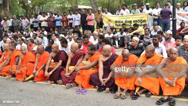 Members of the People's Liberation Front group and Buddhist monks sit at a roadside as they hold a rally calling for calm following deadly communal...