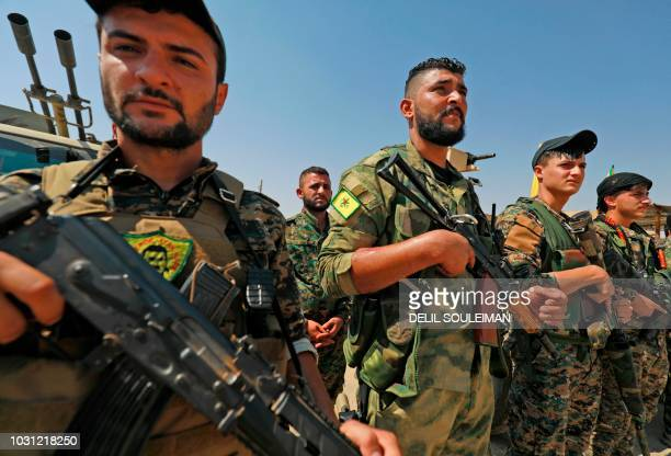 Members of the People's Protection Units part of the of the Syrian Democratic Forces gather in the town of Shadadi about 60 kilometres south of the...