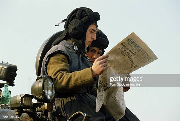 Members of the People's Troops read a copy of Adevarul newspaper in Bucharest during the Romanian Revolution December 1989