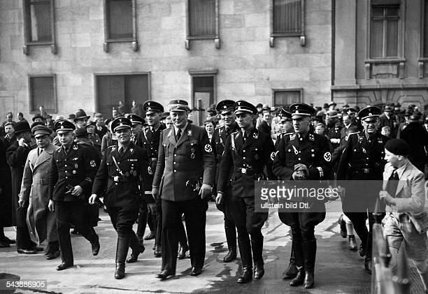 Members of the permanent entourage of Adolf Hitler photographer Heinrich Hoffmann wearing a coat Sturmbanngruppenfuehrer Wernicke Hitler's pilot Hans...