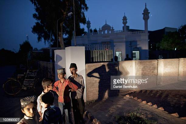 Members of the persecuted Ahmadiyya community gather after evening prayers outside a mosque on July 14 2010 in Chenab Nagar Pakistan The Pakistani...
