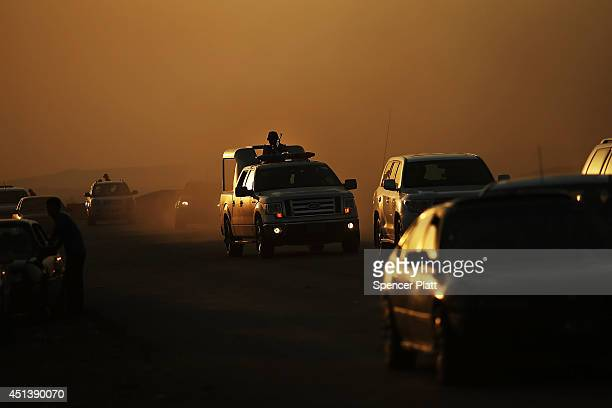 Members of the Peshmerga drive down a street outside of a displacement camp for those caughtup in the fighting in and around the city of Mosul on...