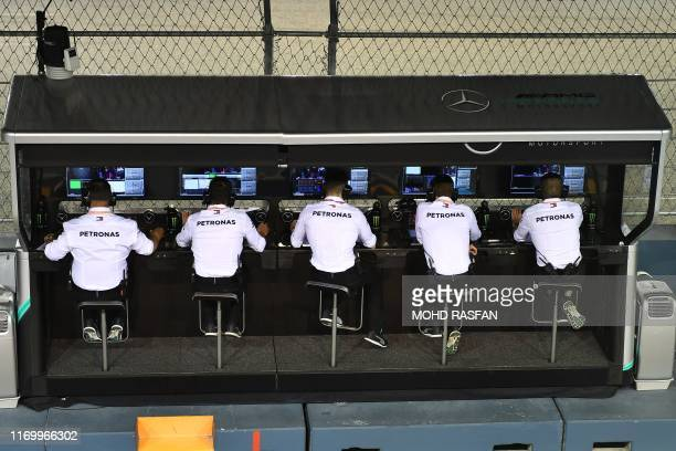 Members of the Petronas team monitor the action during the qualifying session for the Formula One Singapore Grand Prix at the Marina Bay Street...