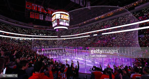 Members of the Philadelphia Flyers and the New York Rangers stand on the ice together for a moment of silence honoring the 20 year anniversary of the...