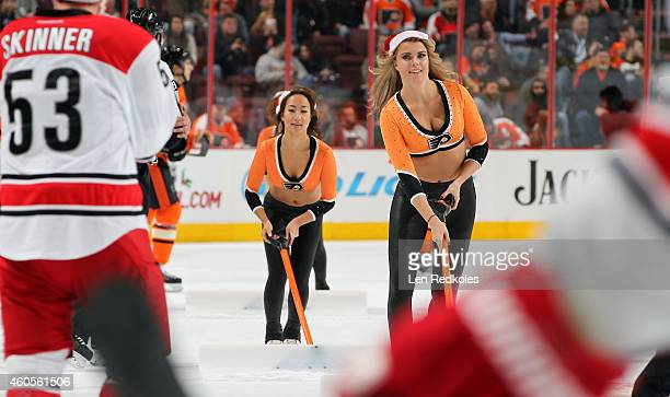 Members of the Philadelphia Flyers ice girls clean the ice during a timeout against the Carolina Hurricanes on December 13 2014 at the Wells Fargo...