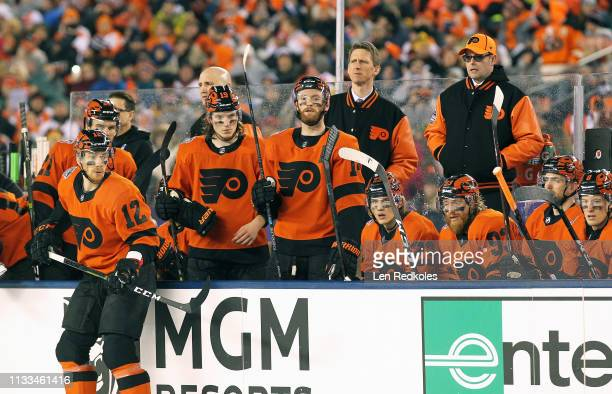 Members of the Philadelphia Flyers react to a play on the ice from their bench against the Pittsburgh Penguins at the 2019 Coors Light NHL Stadium...