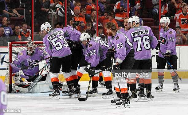 Members of the Philadelphia Flyers wearing lavender jerseys during warmups for Hockey Fights Cancer Awareness Night against the Detroit Red Wings on...