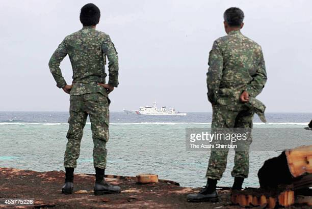 Members of the Philippine Marine Corps stationed at the dilapidated Sierra Madre, watch a Chinese surveillance vessel cruises on August 4, 2014 in...