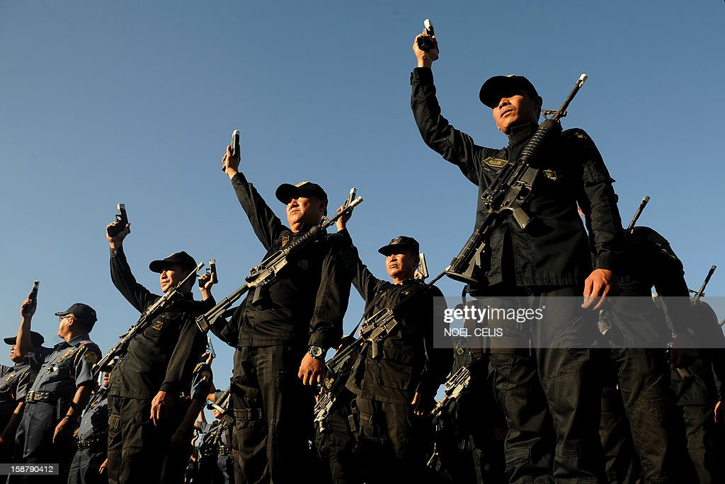 Members of the Philippine National Police (PNP) hold up their firearms with the muzzles taped shut in Manila on December 29, 2012 to prevent any stray gunfire that has plagued the country every New Year's Day. The taping is supposed to ensure that any policeman who fires his gun into the air on New Year's eve will be discovered, the national police chief said.
