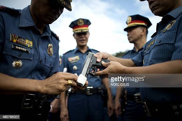 Members of the Philippine National Police seal the muzzles of their guns with tape in Manila on December 22 to prevent any stray gunfire that has...