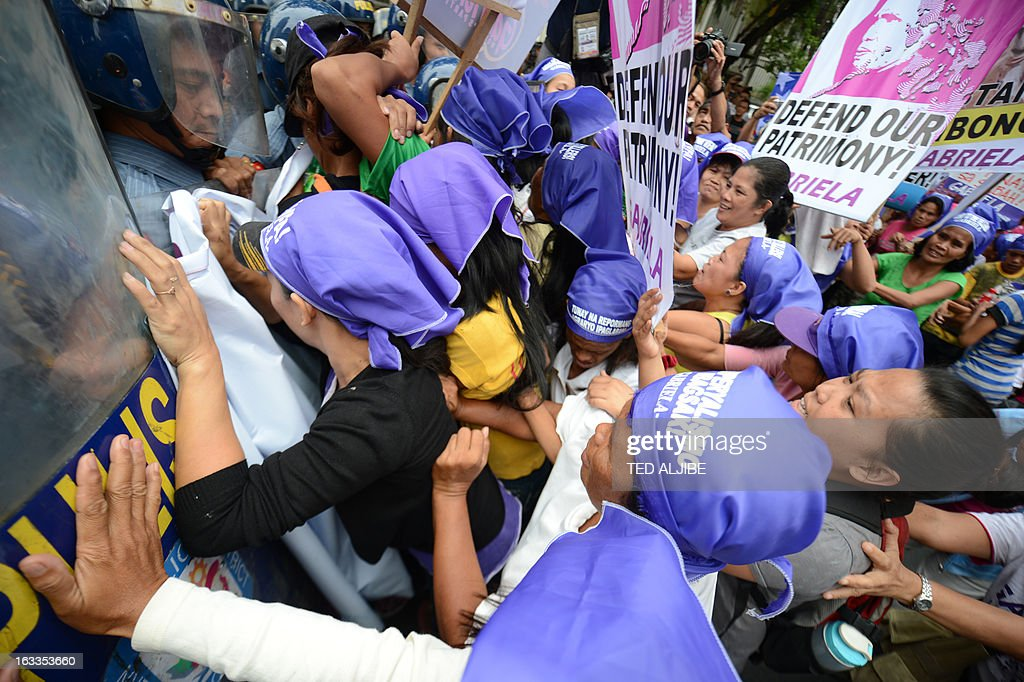 members of the Philippine's women group Gabriela, try to break a police line as they attempt to march to the US embassy for a rally in Manila on March 8, 2013. The protest march was held as part of the Philippine's women group Gabriela, celebration of the International Women's Day.