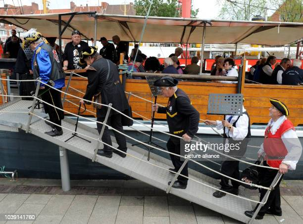 Members of the pirate choir 'Doer Anker' entering the boat 'Stadt Emden' on their way to the next concert during the Herring Days in Emden Germany 27...