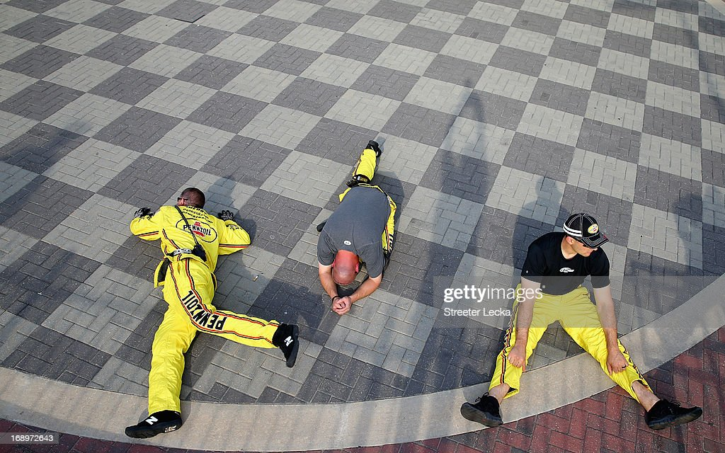 Members of the pit crew for the #22 Pennzoil Ford, driven by Joey Logano stretch prior to qualifying for the NASCAR Sprint Cup Series Showdown at Charlotte Motor Speedway on May 17, 2013 in Concord, North Carolina.