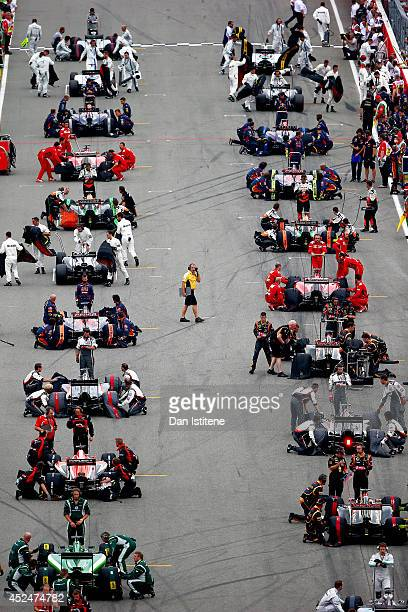 Members of the pit crews prepare to remove the tyre covers prior to the parade lap before the start of the German Grand Prix at Hockenheimring on...