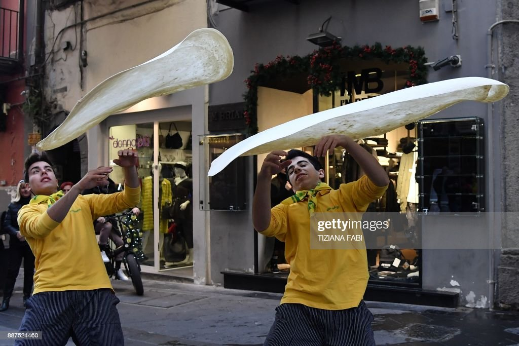 Members of the Pizzaioli Acrobats Coldiretti perform 'twirling' pizza to celebrate the Unesco decision to make the art of Neapolitan 'Pizzaiuolo' an 'intangible heritage', on December 7, 2017 in Naples. The art of the Neapolitan Pizzaiuolo is a culinary practice consisting of four different phases relating to the preparation of the dough and its baking in a wood-fired oven. The practice originates in Naples, where around 3,000 Pizzaiuoli now live and perform, and plays a key role in fostering social gatherings and intergenerational exchange. / AFP PHOTO / Tiziana FABI