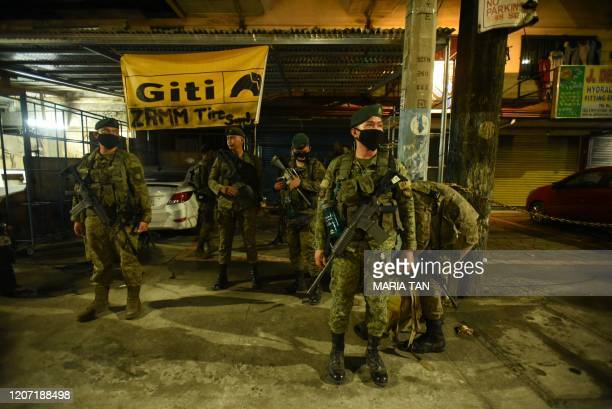 Members of the police and the army stand at a check point to randomly inspect vehicles coming from North Luzon Express way in Manila, in the early...