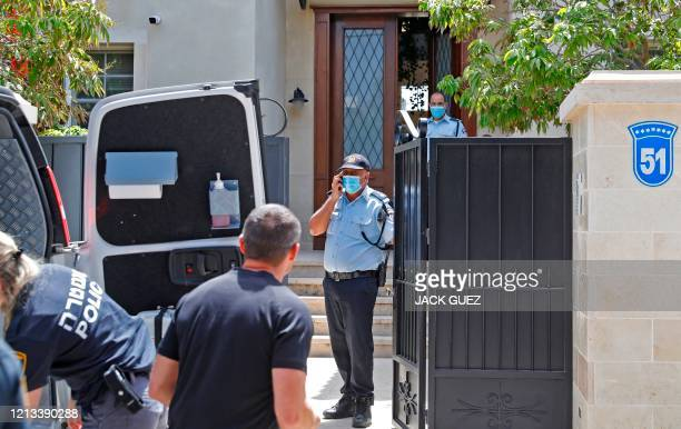 Members of the police gather at the entrance of the residence of Israel's Chinese ambassador on the outskirts of Tel Aviv after he was found dead on...