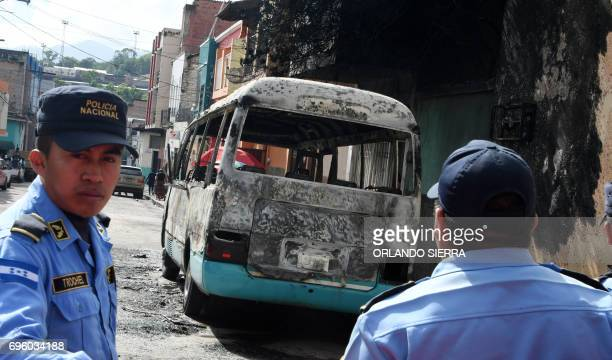 Members of the police investigation division inspect a bus burnt by gang members angry that owners of the companies refuse to pay them a war tax in...