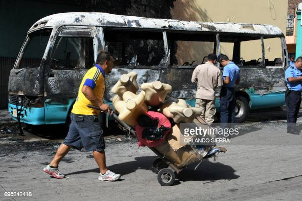 Members of the Police Investigations Division inspect a bus burnt by gang members angry that owners of the companies refuse to pay them a war tax in...