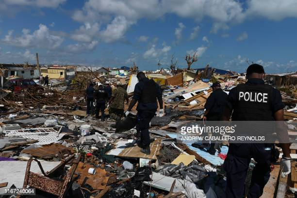 Members of the police join a recovery team looking in the debris in Marsh Harbour Bahamas on September 10 one week after Hurricane Dorian Bahamas...
