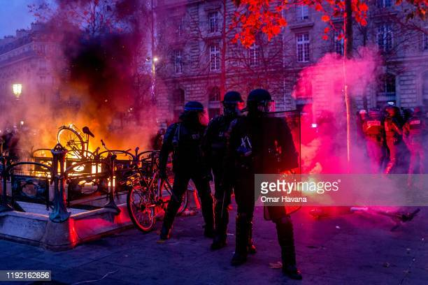 Members of the police regroup after radical groups threw flares towards them during the first day of an indefinite general strike on December 05 2019...