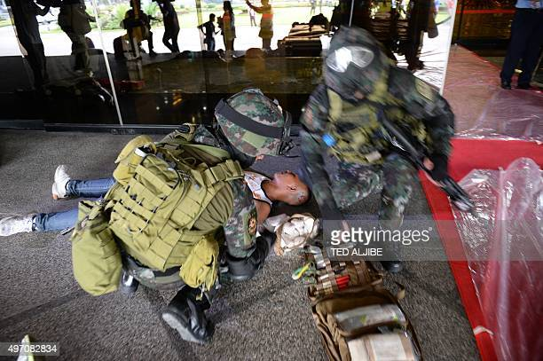 Members of the police Special Action Force attend to a person acting as an injured victim during a drill simulating a Paris-like attack at the...