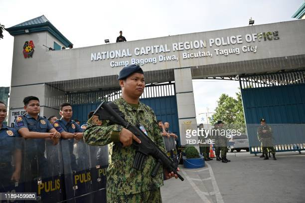 Members of the police special action force stand guard at a gate of the capital command headquarters in Manila on December 19 ahead of a court...
