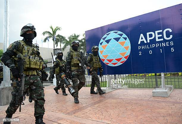 Members of the police Special Action Force walk in front of signage for the Asia-Pacific Economic Cooperation summit after a drill simulating a...