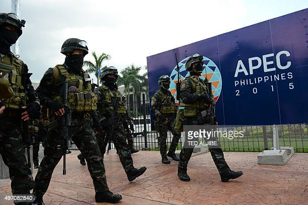 Members of the police Special Action Force walk in front of signage for the AsiaPacific Economic Cooperation summit after a drill simulating a...