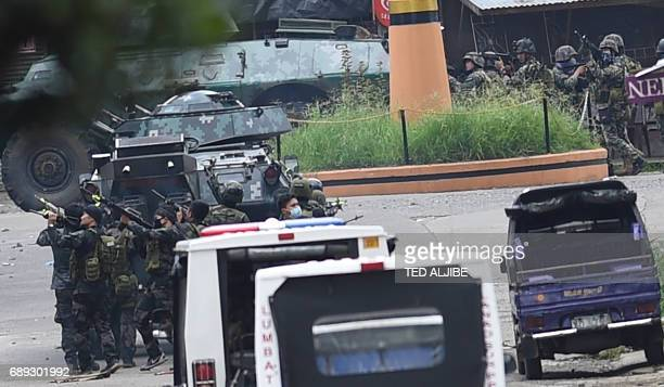 Members of the police special forces manueover as they assault Muslim militants' hide out near the city hall in Marawi in southern island of Mindanao...