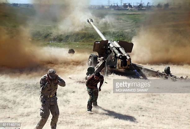 TOPSHOT Members of the Popular Mobilisation Units progovernment paramilitaries forces cover their ears as they fire a multiple rocket launcher during...