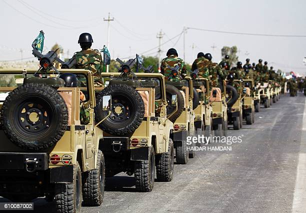 Members of the Popular Mobilisation Units supporting the government forces drive military vehicles on the outskirts of the holy Iraqi city of Najaf...