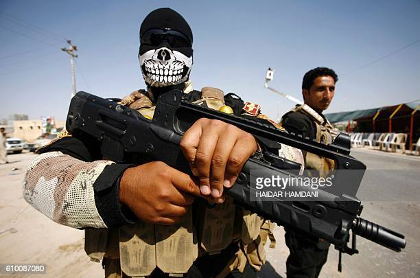 TOPSHOT Members of the Popular Mobilisation Units supporting the government forces stand on the outskirts of the holy Iraqi city of Najaf on...