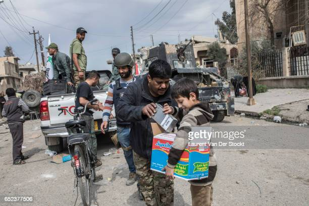 Members of the popular shiite mobilization are distributing food and cigarettes in the districts of western Mosul taken back by the the Iraqi...