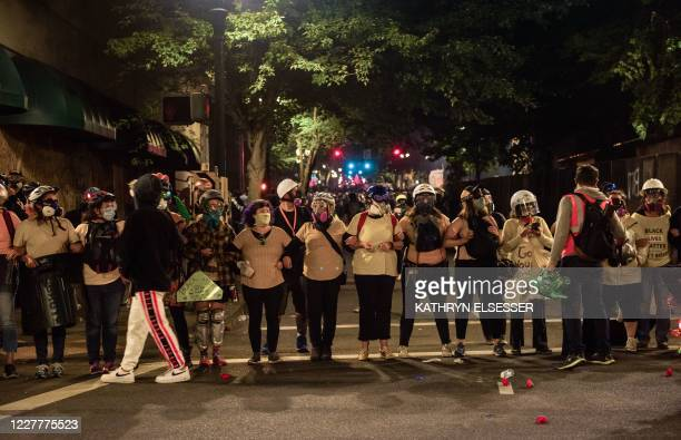 """Members of the """"Portland Mom Brigade"""" link arms as they take part in a rally against police brutality in Portland, Oregon late July 24, 2020. -..."""