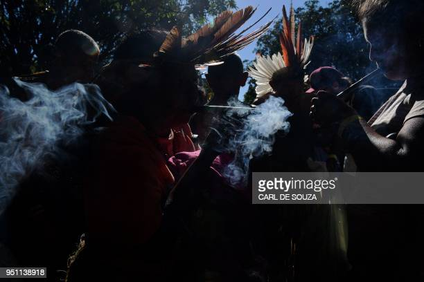 TOPSHOT Members of the Potiguara tribe smoke during a ceremony at the Acampamento Terra Livre in Brasilia on April 25 2018 Approximately 2500...