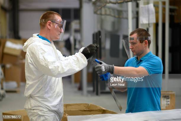 Members of the powder coating team wear protective face masks as they work in close proximity with each other at the HL Display factory on May 19,...