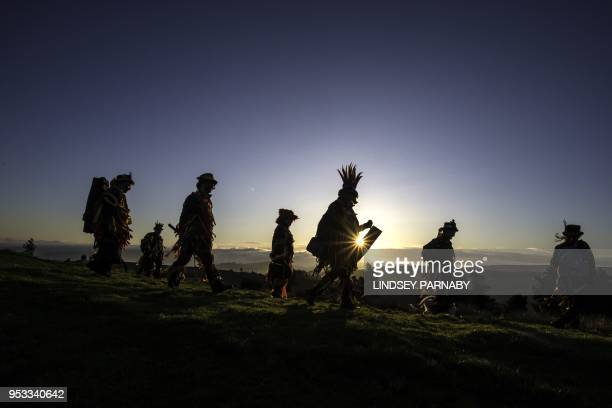 Members of the Powderkeg Morris Dancers climb down after dancing atop the Windgather Rocks at High Peak in Derbyshire before sunrise on May 1 2018...