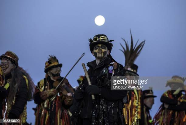 TOPSHOT Members of the Powderkeg Morris Dancers climb down after dancing atop the Windgather Rocks at High Peak in Derbyshire before sunrise on May 1...
