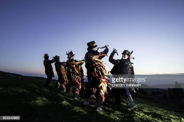Members of the Powderkeg Morris Dancers dance atop the Windgather Rocks at High Peak in Derbyshire before sunrise on May 1 2018 The Powderkeg Morris...