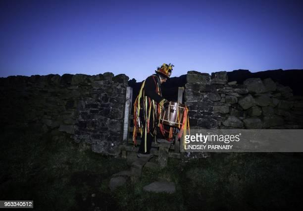 Members of the Powderkeg Morris Dancers walk up the Windgather Rocks at High Peak in Derbyshire before sunrise on May 1 2018 The Powderkeg Morris...