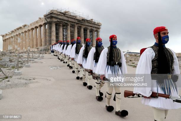 Members of the Presidential Guard walk in front of the Parthenon temple atop of Acropolis Hill after the Greek flag raising ceremony in Athens, on...