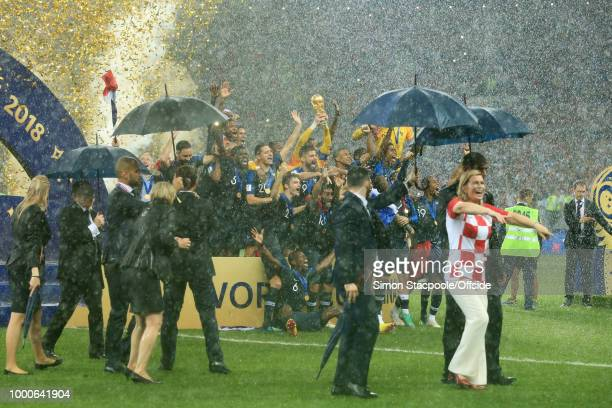 Members of the Presidential security detail walk off the pitch holding umbrellas in the rain as France goalkeeper Hugo Lloris lifts the trophy to...