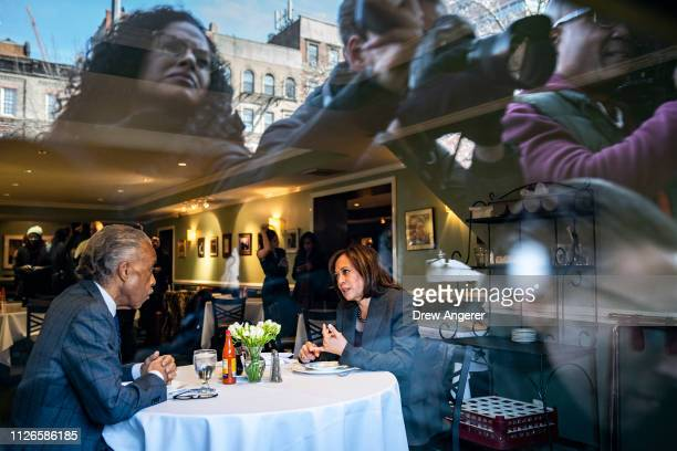 Members of the press are reflected in a window as Rev Al Sharpton and 2020 Democratic presidential candidate Sen Kamala Harris talk while having...