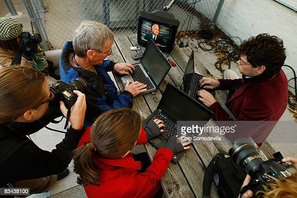 Members of the press corps traveling with Republican presidential nominee Sen John McCain take notes on computers while watching a small television...