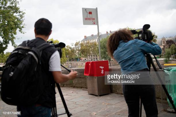 Members of the press film a uritrottoir public urinal on August 13 on the SaintLouis island in Paris The city of Paris has begun testing uritrottoirs...