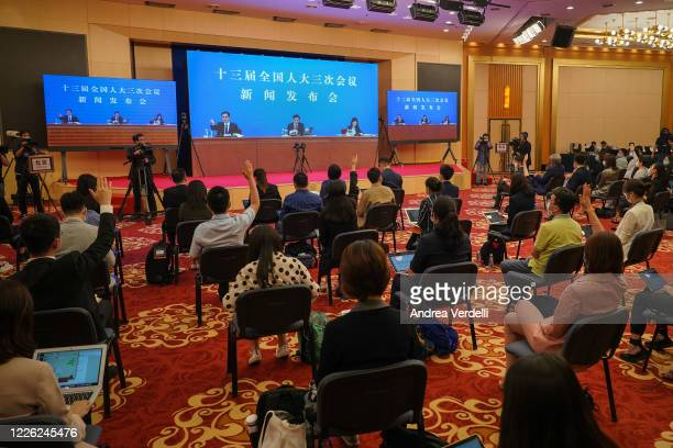 Members of the press, located at the Media Center, raise their hands to ask questions to the spokesperson for the National People's Congress Zhang...