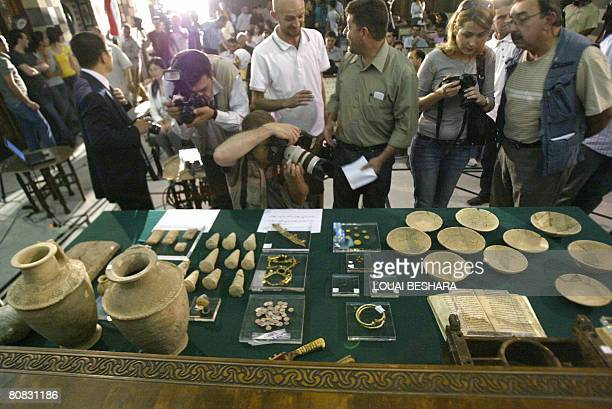 Members of the press look at some of the 700 Iraqi antiquities which have been in the care of Syria authorities at the National Syrian Museum in...