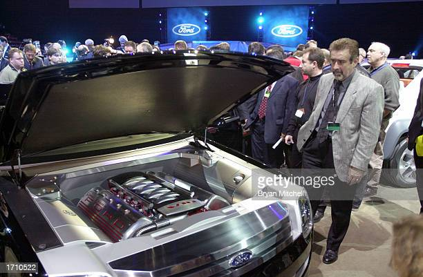 Members of the press look under the hood of the Ford 427 concept car after a press conference at the North America International Auto Show January 5,...